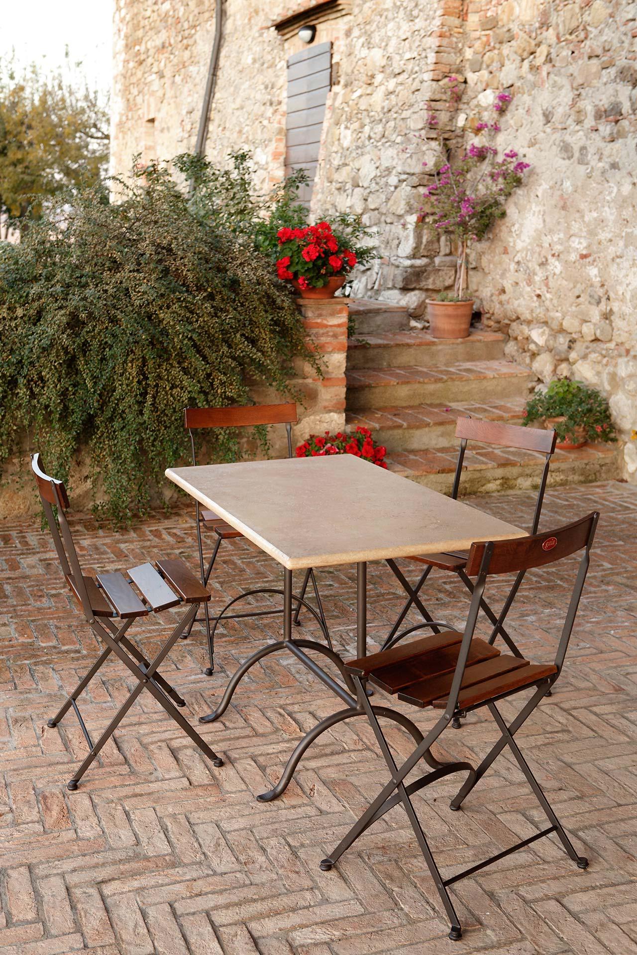 tavolo Bistrot con piano in travertino, sedia Carlotta seduta e schienale in legno